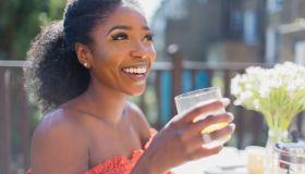 Happy young woman drinking orange juice on sunny balcony