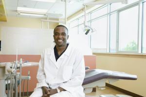 Male dentist sitting by dentist's chair, portrait