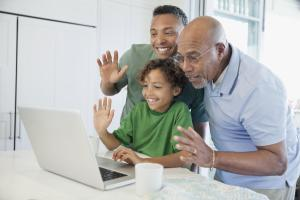 Happy boy with father and grandfather having video chat on laptop